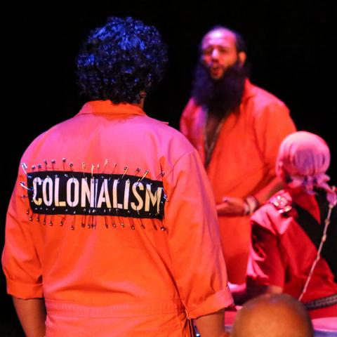 "A man in an orange jumpsuit has pinned the word ""Colonialism"" to the back of it."