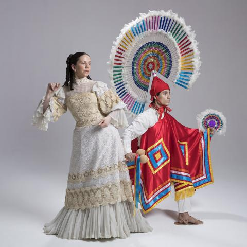 A man and a woman pose in traditional Mexican garb in a white walled studio space