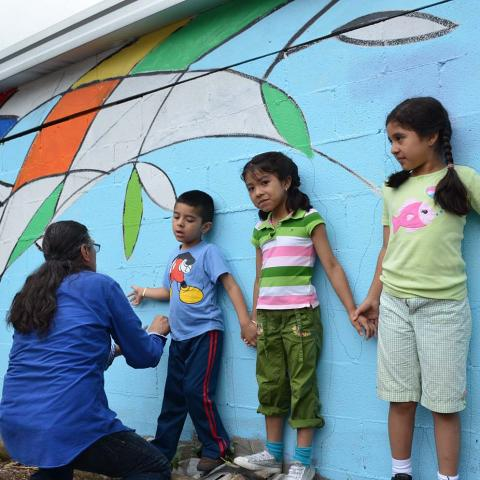 A woman leans down to help a young boy who leans against a mural with two young girls.