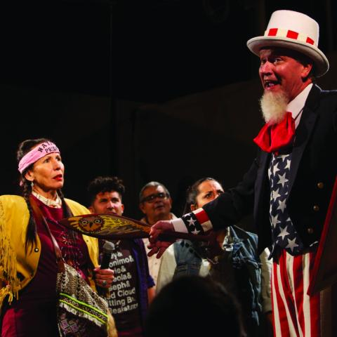 A man in an Uncle Sam outfit stands before a dissappointed crowd, one dressed in traditional Native American garb.
