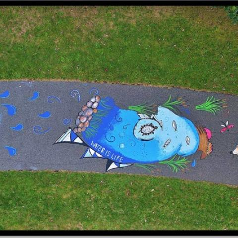 Overhead view of a sun, sea, and earth chalk mural on pavement.