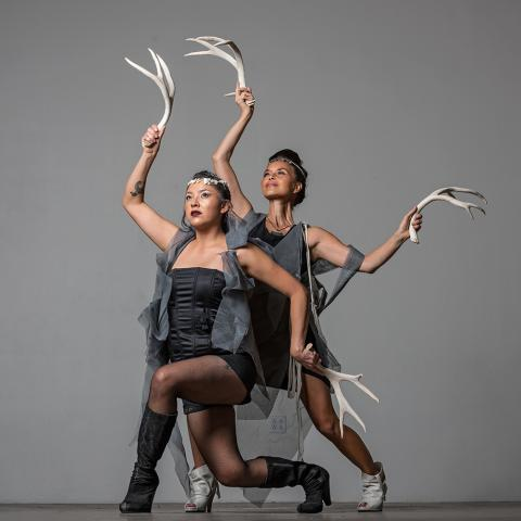 Two females dance in front of a gray backdrop with antlers in their hands.