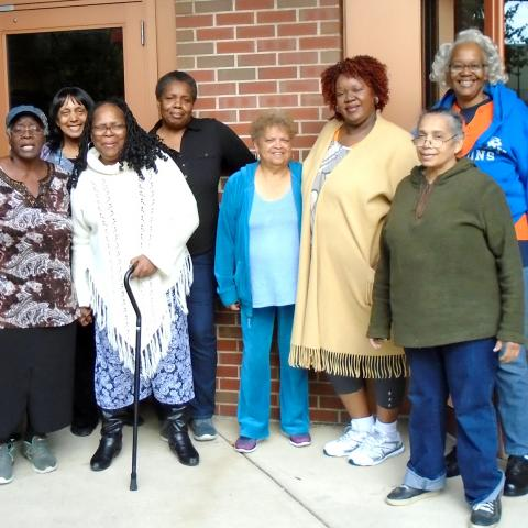 A group of women of color pose in front of a brick building.