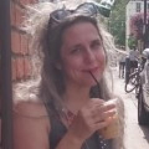 Karen sips iced coffee and smiles on a street corner