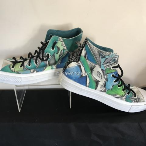 A pair of high top sneakers embellished with a graphic design using blue, green, black and grey colors.