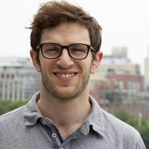 A young man with a short beard and glasses; the backdrop includes the trees of Boston Common and buildings in Back Bay.
