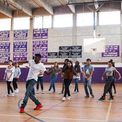 In a high school gymnasium, a man in a white tee leads a group of students in a dance.