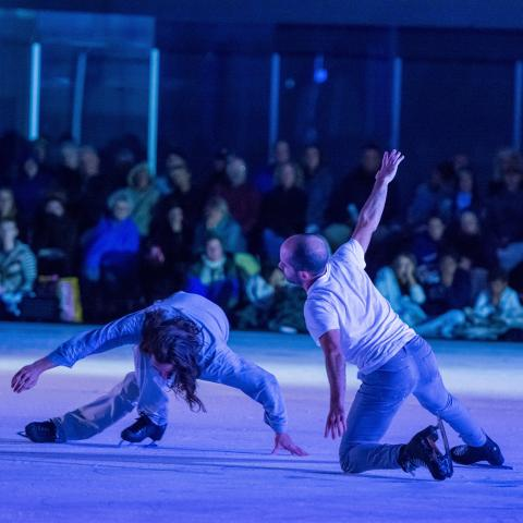 Two male figure skates or ice dancers perform low to the ice.