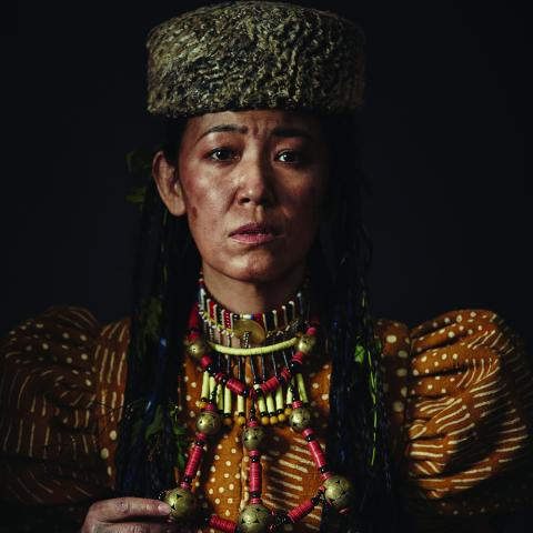 A women in a thick beaded necklace and a flat hat stares solemnly