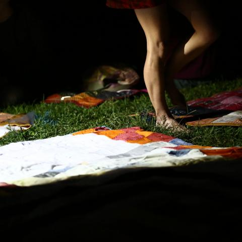 A woman walks over fabric laid over grass.