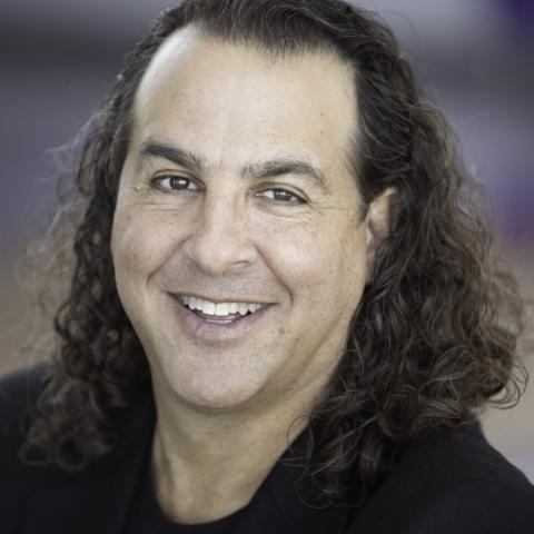 A man with long curly hair and sporting a black suit jacket smiles.