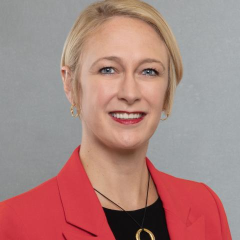 A woman with short blonde hair wearing a red blazer and black shirt.