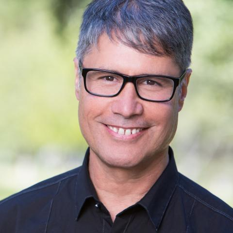 A man with short gray hair and dark framed glasses wearing a dark button down shirt