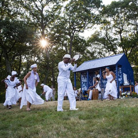 Ife stands in front of a cabin that is wrapped in fabrics dyed in indigo. A crowd, dressed all white, dance around her.