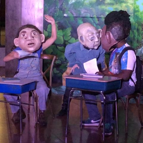 Wearing over-sized masks, three performers sit behind desks.