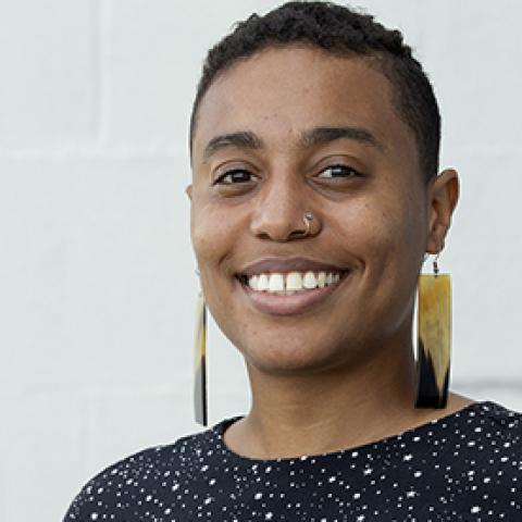 A smiling person with short hair and chunky earrings