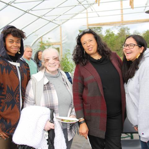 Artist Nia Holly (Nipmuc), Gail Rokotuibau (Narragansett/Pequot), Dawn Spears (Narragansett/Choctaw), and Samantha Fry (Narragansett) stand together and smile facing the camera inside a high tunnel at the Markets & Marketing workshop