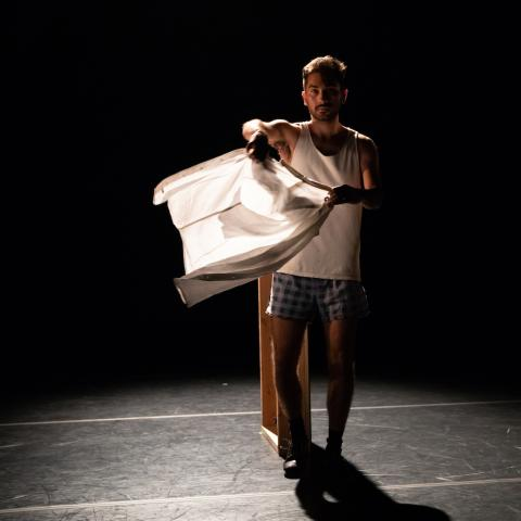 A man stands in a darkened black box theater in an undershirt and boxers waving a white tee shirt like a flag