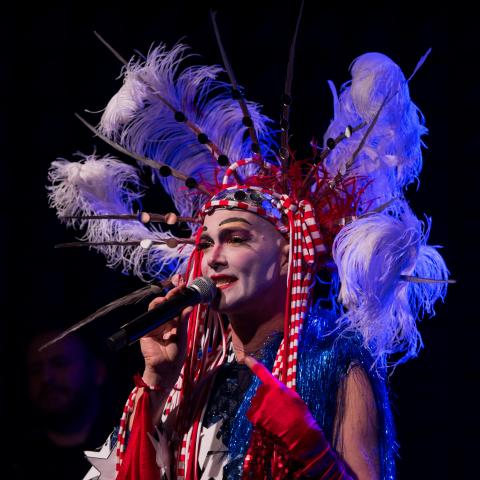 The artist holding a microphone and wearing an elaborate red, white, and blue costume with feathers, stars, and sparkles.