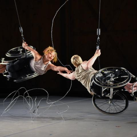 Alice, a dancer with light brown skin and short curly hair, and Laurel, a dancer with pale skin and close-cropped blonde hair, hang from the ceiling. They each have one hand on a cable as they reach for each other with the other. They are nearly horizontal and their legs and feet face out. Silver barbed wire stretches between and beneath them, against the black backdrop.