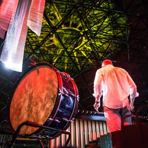 From behind and below, a man stands next to a large drum, amid colorful spotlights.
