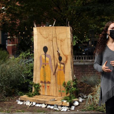 Lily, in a face mask, speaks next to an installation, two Native American women painted on a shaved tree trunk.
