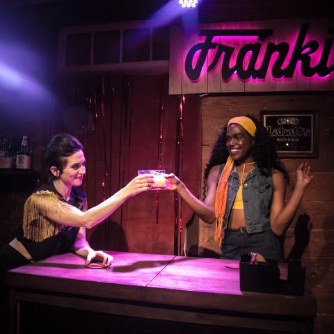 "Two women stand by a bar that says ""Frank's"" in neon behind them,"