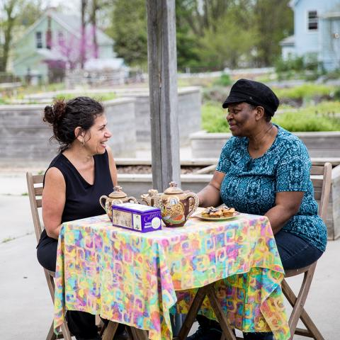 Two women sit at a table in a park.