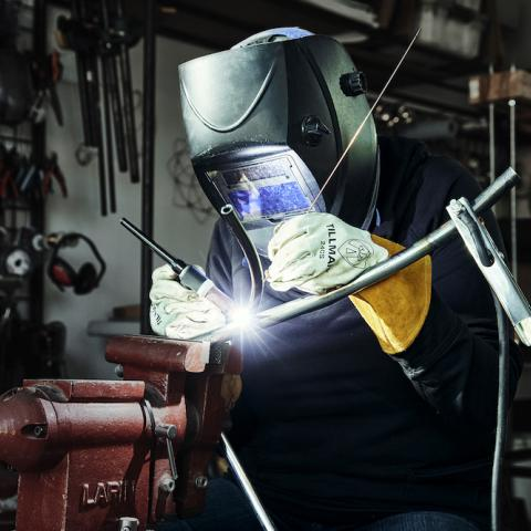 A craftsperson welds metal while wearing a protective mask and gloves