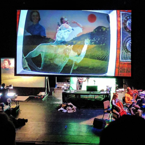 Puppeteers and an orchestra are on either side of a projection of a TV that shows a character running.