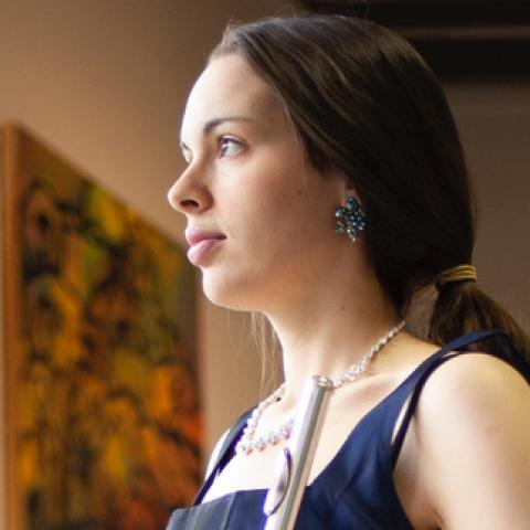 Melissa has long brown hair, pulled back into a loose ponytail. She wears a pearl necklace and big blue earrings.
