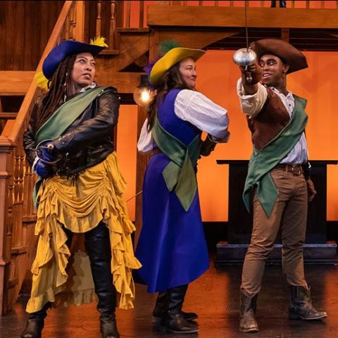 On a stage, four actors of color are dressed as muskateers.