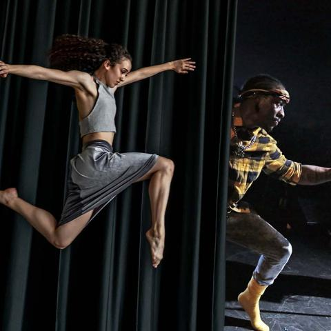 A dancer leaps before a curtrain. Behind the curtain, the a guitarist and dancer.