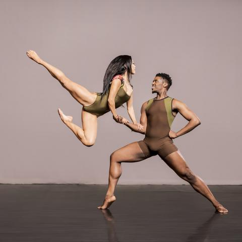 In front of a gray backdrop, one dancer leaps while the other dancer supports them with just one arm.