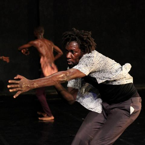 A man thrusts his arm out while other men dance in the background