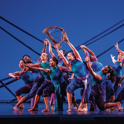 On a stage, a troupe of dancers wear blue and purple in front of a blue backdrop.