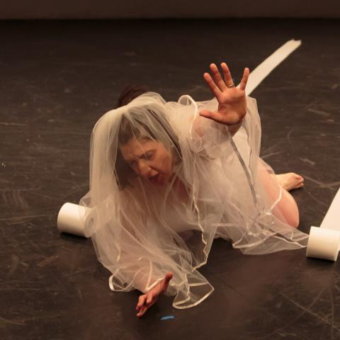 Sara lays on the ground, wearing a bridal veil, and raises her hand up as if to reach.
