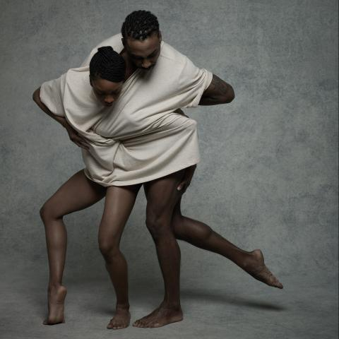 Two dancers share one t-shirt and each have an arm coming out of one of the sleeves. Both dancers are looking down.