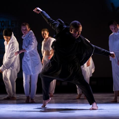 A man in black dances in the foreground while dancers in white dance in the background.