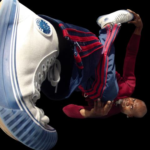 With the lens by the bottom of a Raphel's shoe lifted off the ground in the foreground as he break dances