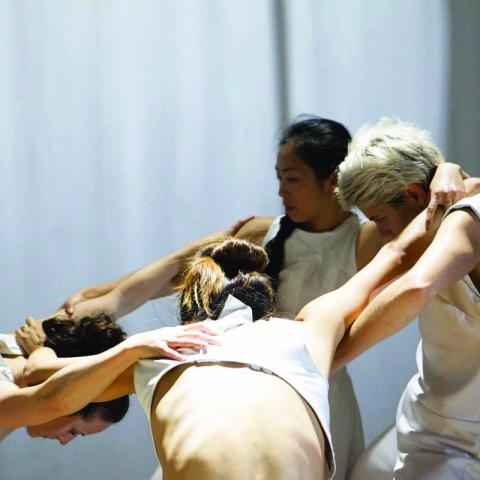 Four dancers in white are in a huddle.