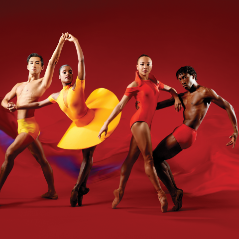 Dancers in bright orange and red outfits dance in a red void