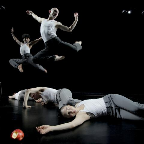 Two male dancers leap behind three female dancers who are unconscious next to an apple with a bite taken out of it.