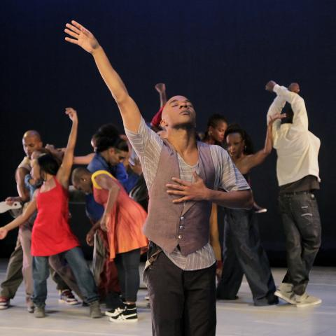 A man in a vest throws his arm up in the foreground and in the background a group of dancers move in a circle.