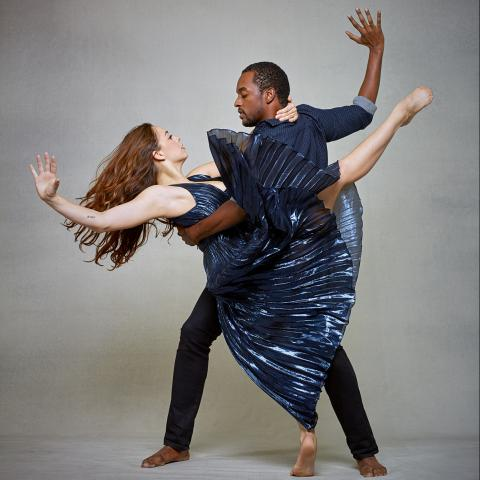A man and woman dance in front of a gray backdrop.
