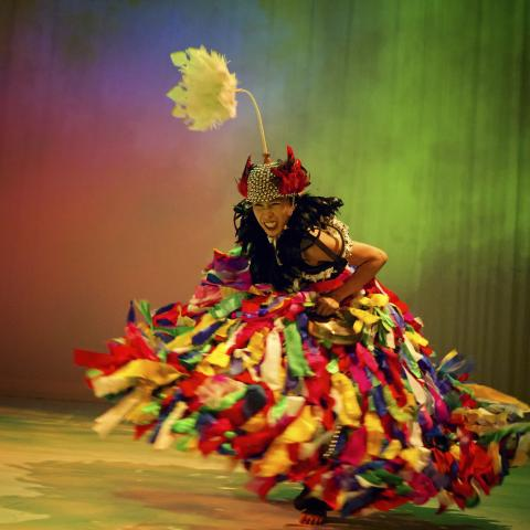 A woman in a multicolored gown dances in a space that reflects multicolored light like a rainbow