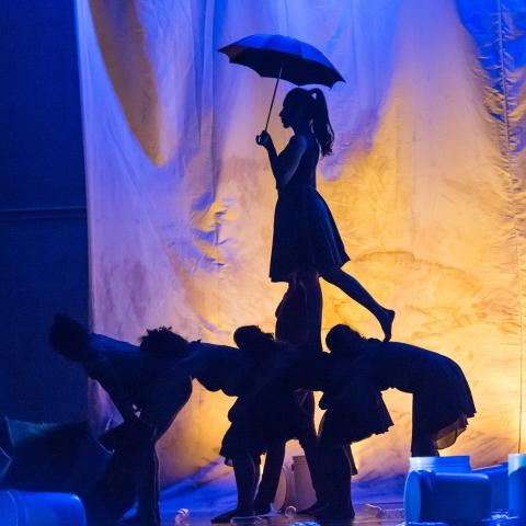 A woman with an umbrella walks over the backs of other dancers leaned over. They're back lit by a yellow lamp in a blue space.