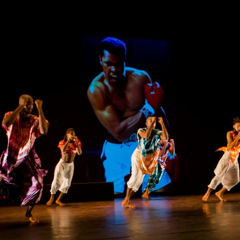 Four dancers perform in front of a projection of Muhammad Ali.