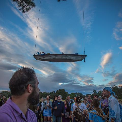 A boat hangs in the air as if it is floating over a group of people, outside.