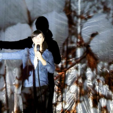 Lit by a projection of wheat, a woman holds her arm out while wearing a jean jacket.